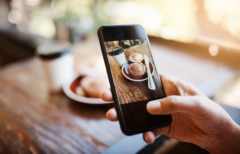 Person taking photo of their breakfast at a cafe