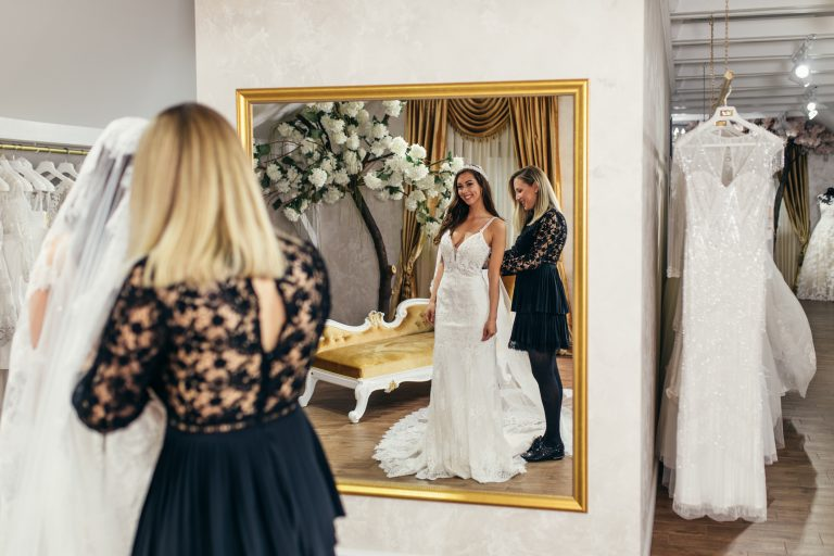 Attractive young brunette bride is smiling and enjoying while choosing wedding dress in modern wedding salon together with another woman worker or seller.
