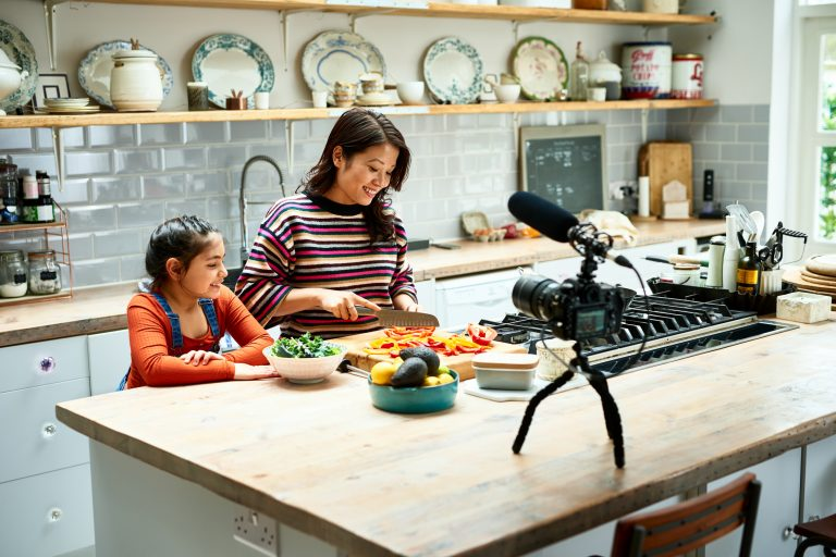 Woman vlogging at home with video camera on worktop and girls watching, food, family, teaching