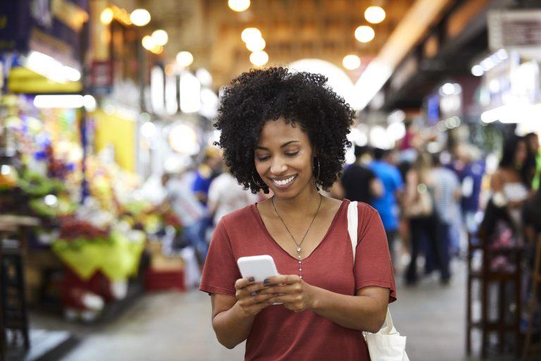 Smiling woman using smart phone at supermarket
