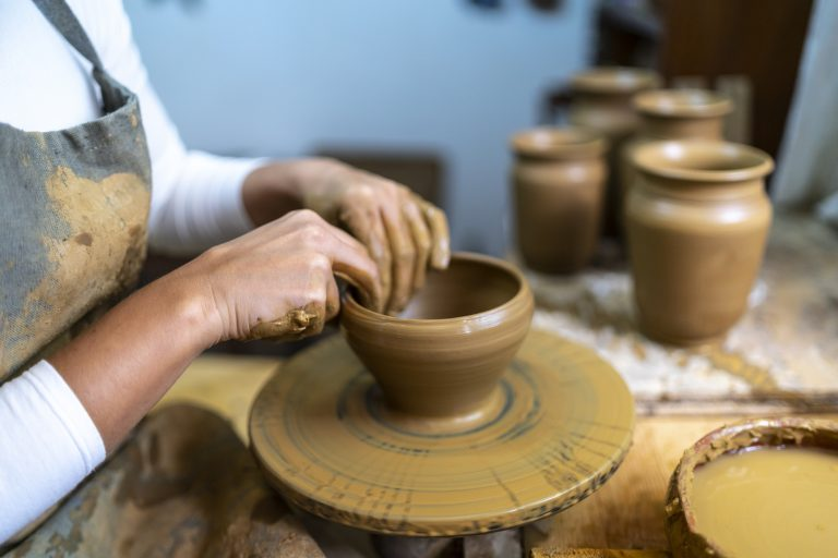 Middle aged woman making ceramic work with potter's wheel