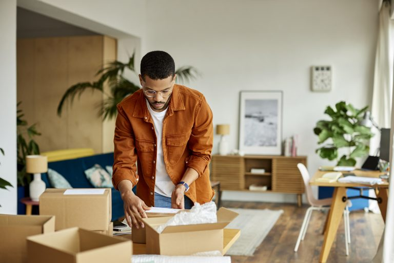 Young businessman packing cardboard box at table in apartment. Male professional is working at home office. He is in living room.