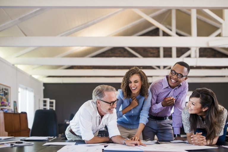 Happy multi-ethnic business people analyzing blueprint in creative office