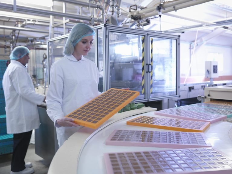 Worker inspecting moulded chocolates in chocolate factory