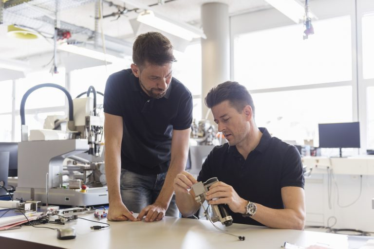 Two men examining product in factory