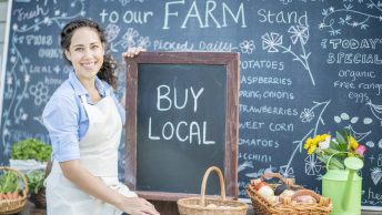 "A portrait of a young woman who is wearing an apron and holding a chalkboard that says ""BUY LOCAL"". She is sitting on a table that features baskets with fresh eggs and produce."