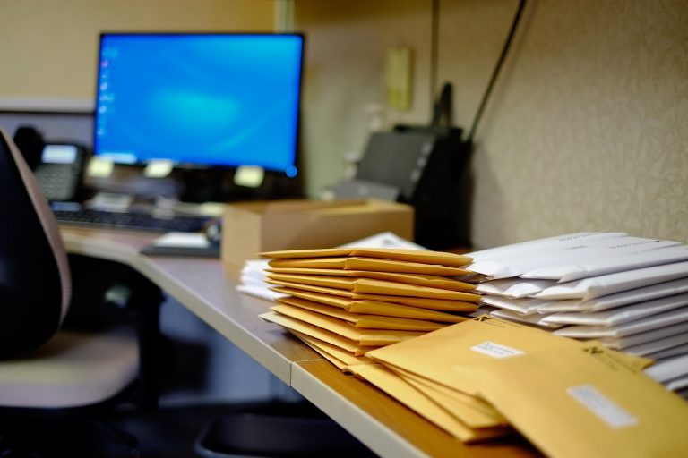 Office desk piled with mail