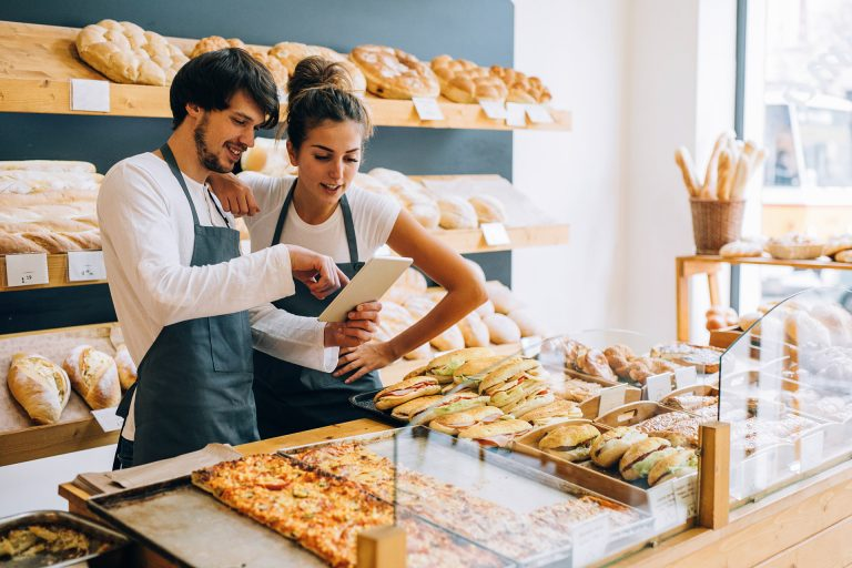 Man and Women looking at tablet in bakery