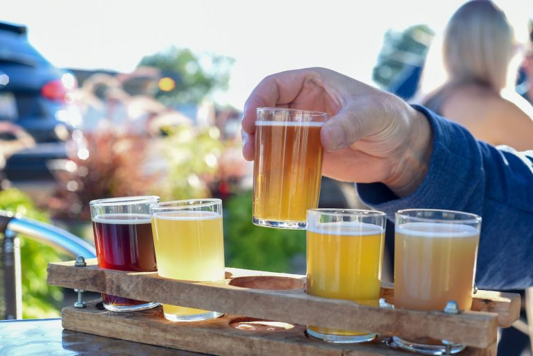 Man sampling a variety of seasonal craft beer at an outdoor beer garden, hands only