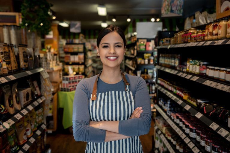 Confident female business owner of a supermarket standing between shelves while facing camera smiling