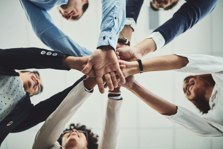 a group of businesspeople forming a huddle with their hands