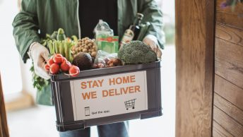 Delivering food ordered online while in home isolation during quarantine. Stay home we deliver sign on box.