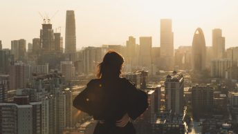 Rear view of Woman looking at city in Sunlight