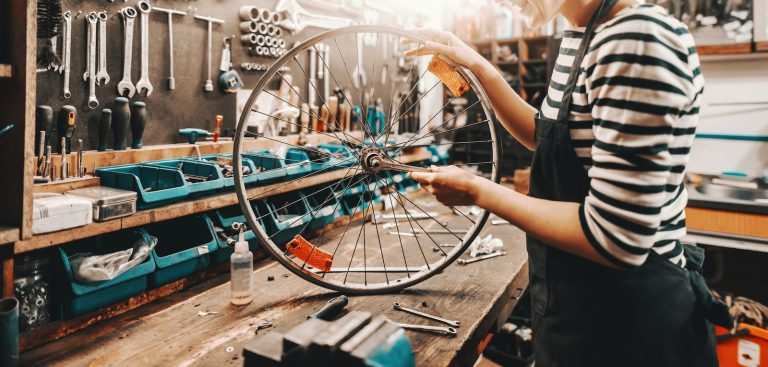 Person holding and repairing bicycle wheel while standing in bicycle workshop.