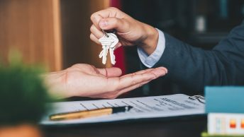 Broker giving keys signed agreement in office