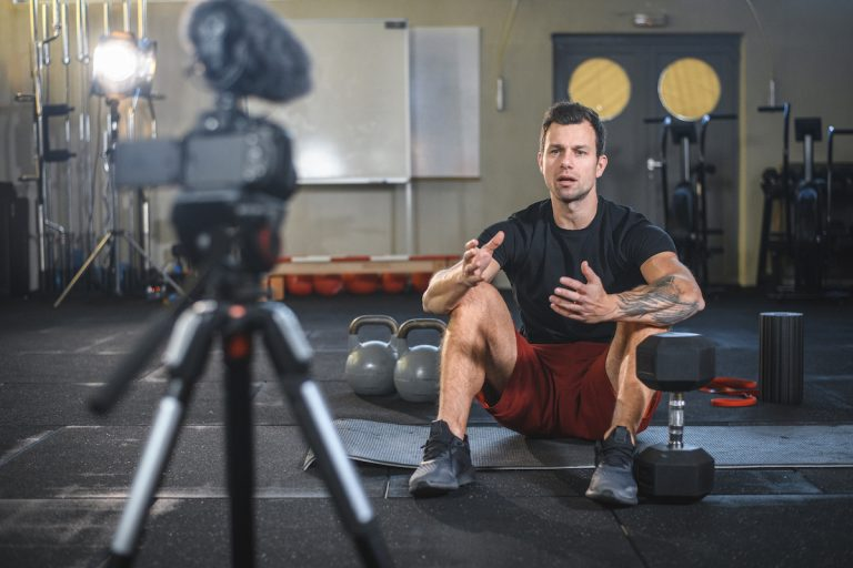 Male Athlete Sitting on Exercise Mat and Making Vlog at Gym