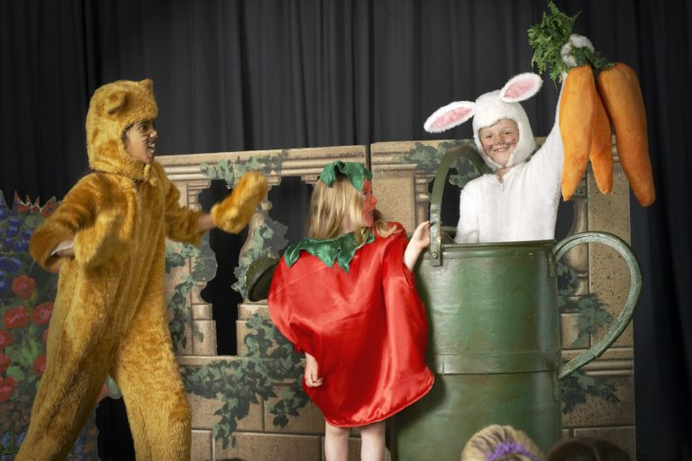 Three children (5-9) in food and animal costumes performing on stage