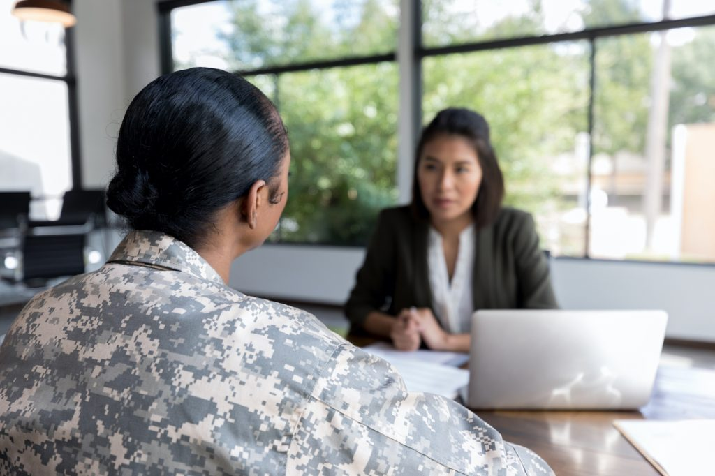 Rear view of female veteran talking with counselor
