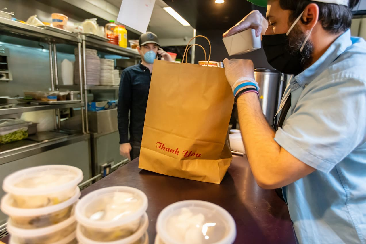 Restaurant owner packing a to go order with a mask on