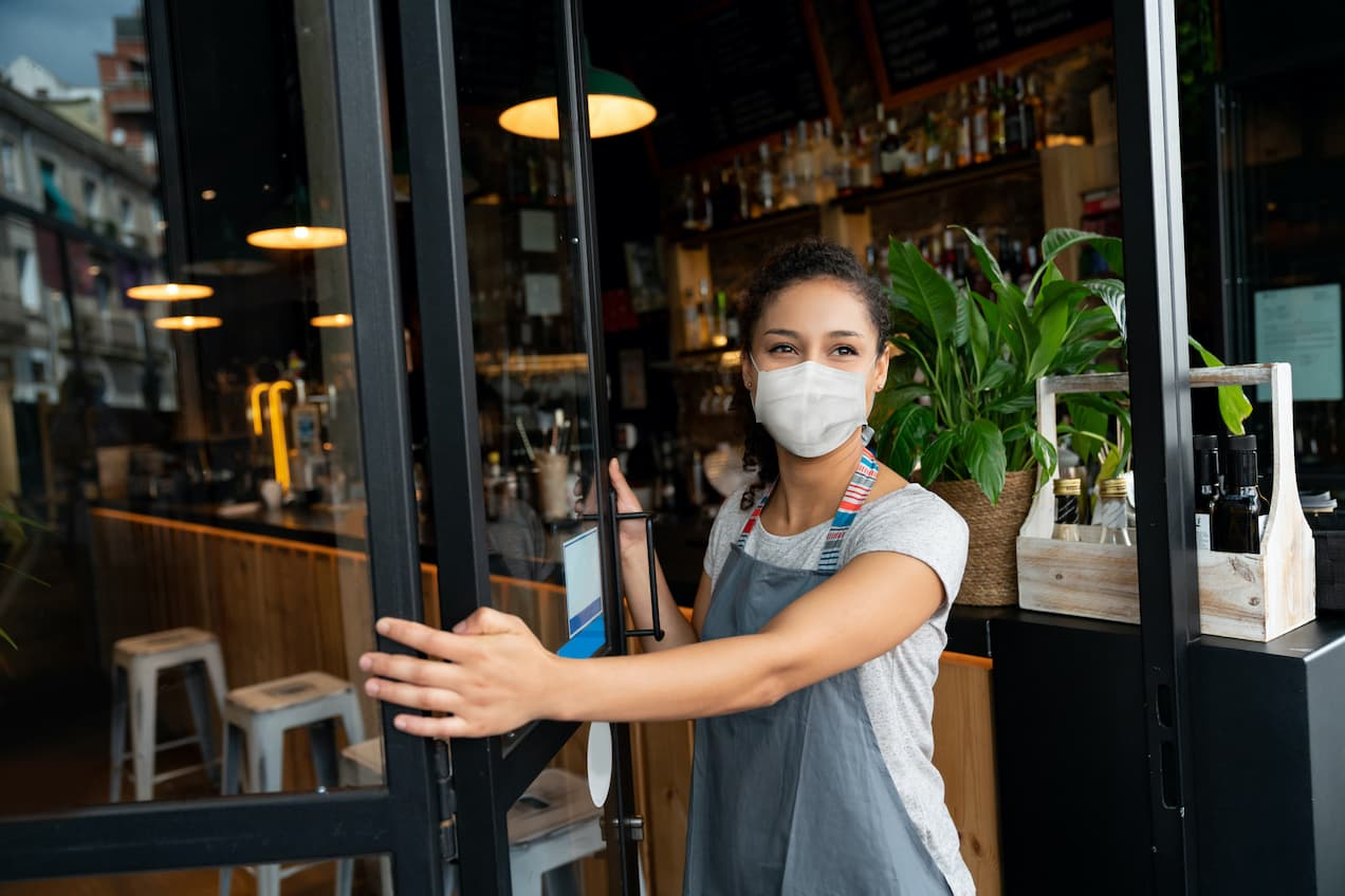 Bartender opening door with mask