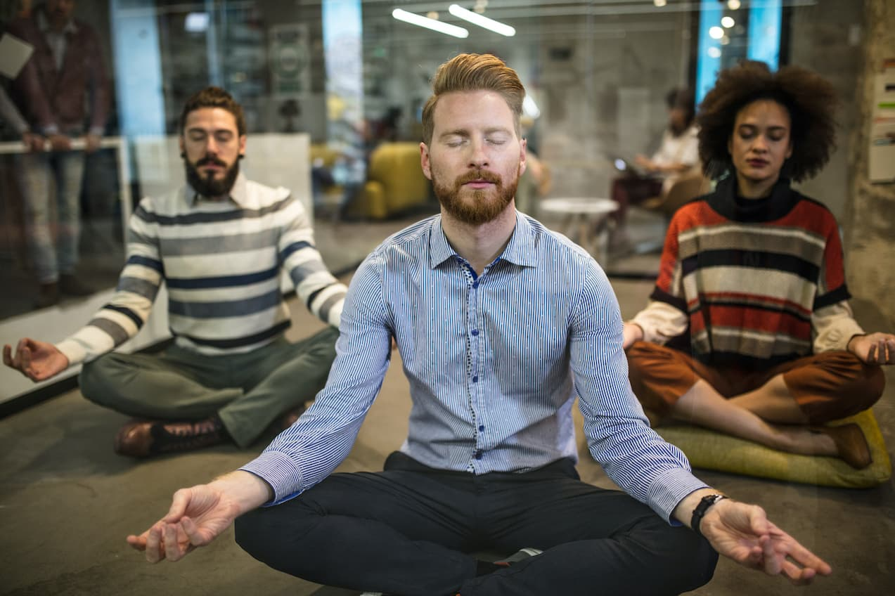 Business people meditating in an office