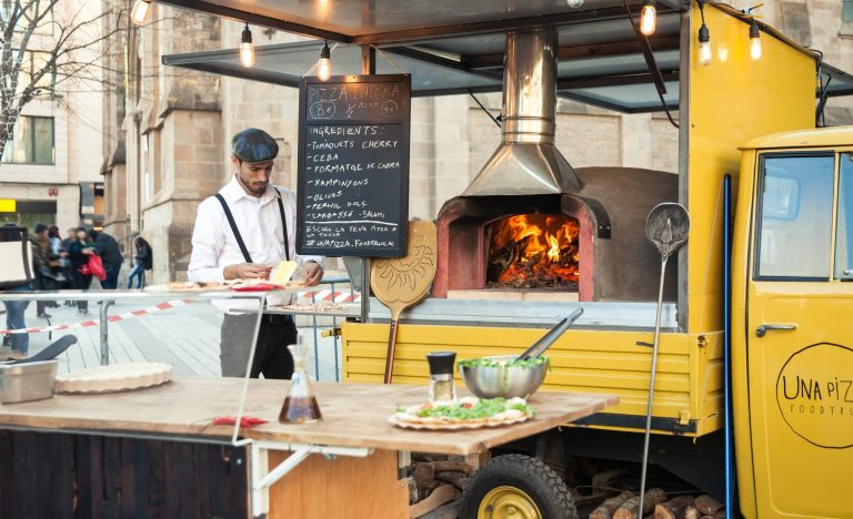 Man making woodfired pizza at a food truck