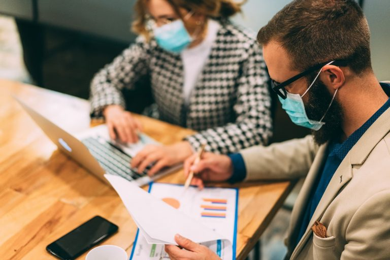 Business people wearing masks and looking at metrics