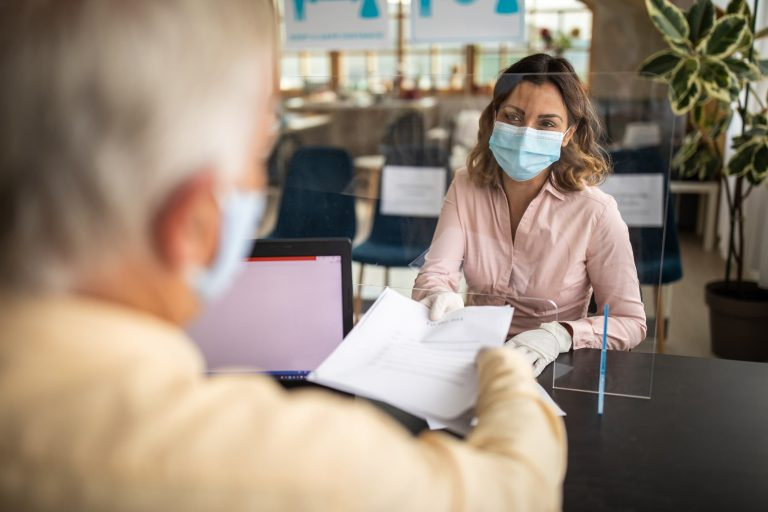 Woman with a medical mask on submitting paperwork