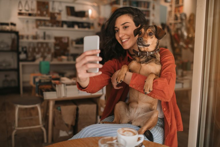 Woman taking a selfie with her dog in a cafe