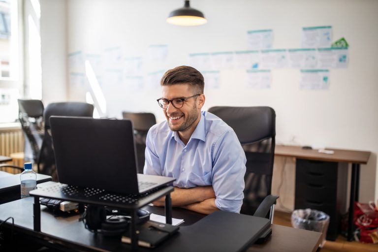 Business owner smiling at their computer