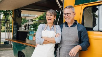Two senior food truck owners laughing