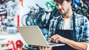 Bike shop owner buying domains on his laptop